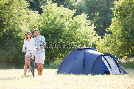 couple sitting with bike in countryside