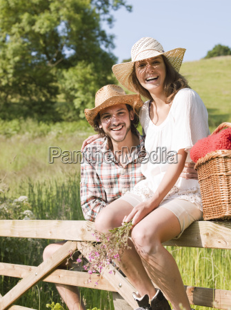 man and woman sitting on country