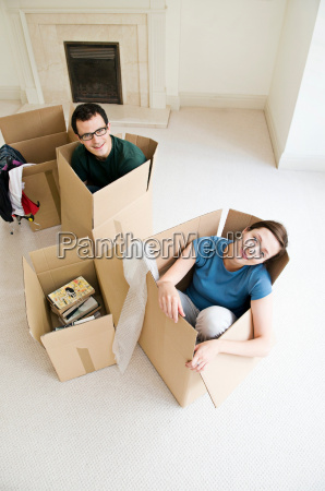a couple sitting in cardboard boxes