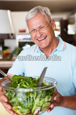 senior man holding salad