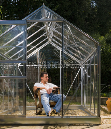 man relaxing in greenhouse