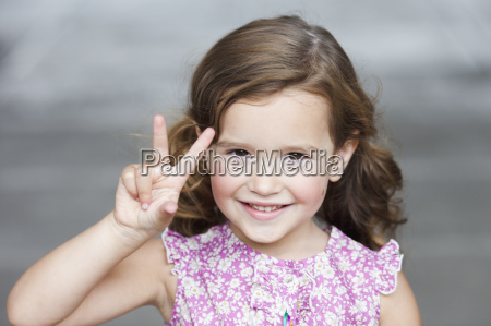 young girl holding up three fingers