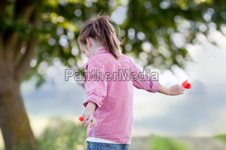 young girl playing with flowers
