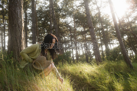 woman crouching engaging in nature