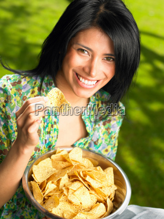 woman eating chips outdoors