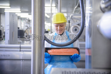 worker inspecting salmon fillet in food