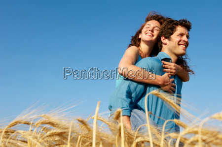 man carrying woman in a wheat