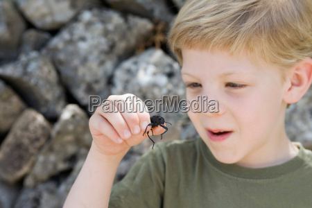 a young boy holding a beetle