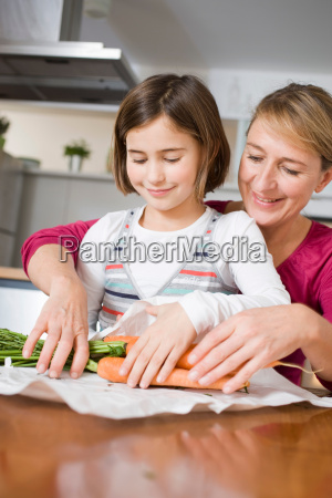 mother and daughter preparing carrots