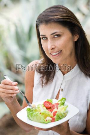 a female eating salad outside