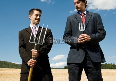 two men holding garden tools