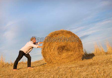 man pushing hay bale