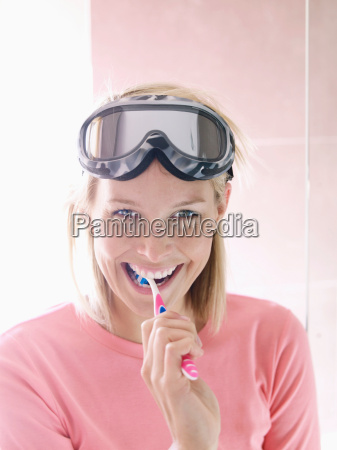 woman in ski gear brushing teeth