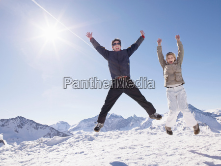 man and woman jumping up on