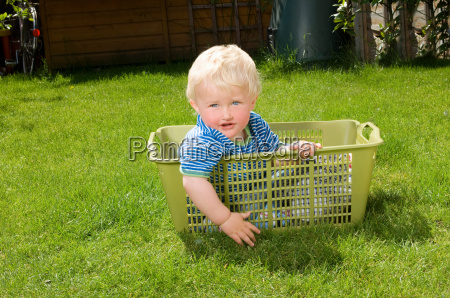 young boy sitting is washing basket