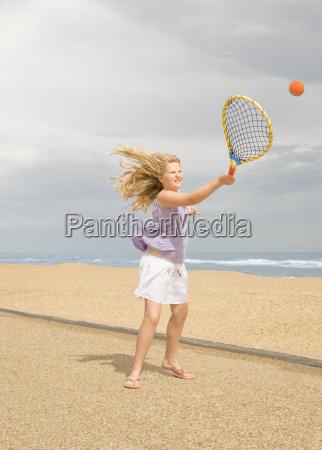 girl playing tennis on promenade
