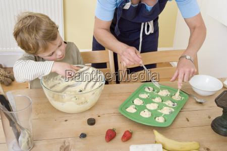boy and mum making fruit muffins