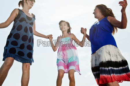 mother grandmother daughter jumping