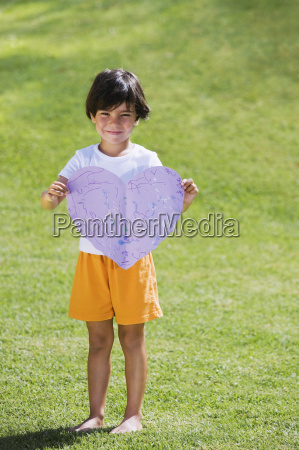 young boy holding purple paper heart