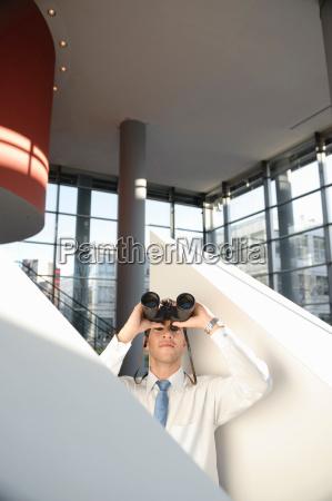 man looking through binoculars in office