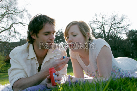 couple blowing bubbles in grass at