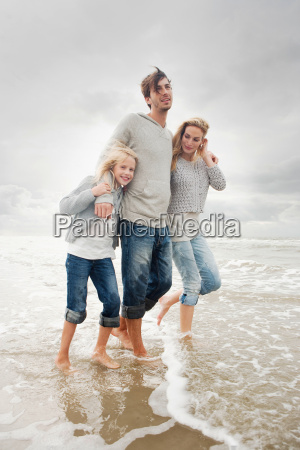 young family on beach in autumn
