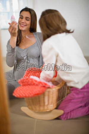 pregnant woman playing with little girl