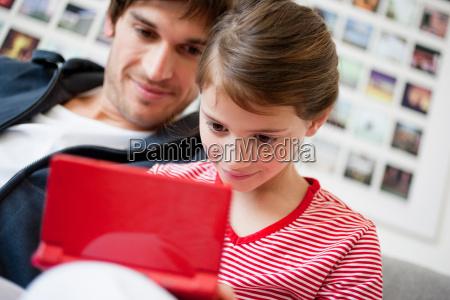 girl playing video game dad watching