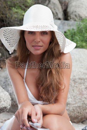 woman in sunhat holding cell phone