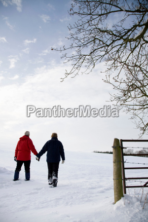 senior couple walking in the snow