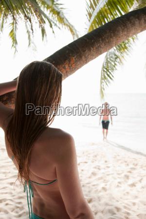 woman admiring man on tropical beach