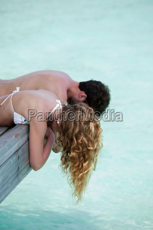 couple laying on deck overlooking water