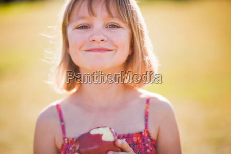 young girl with apple smiling