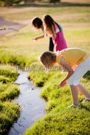 3 young girls looking in creek