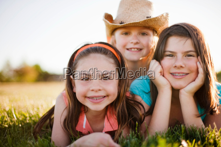 3 young girls laying in grass