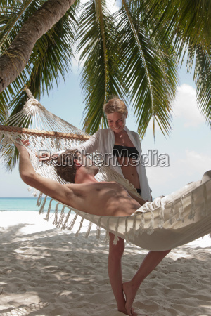 couple relaxing with hammock on beach