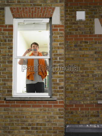 man brushing his teeth in window
