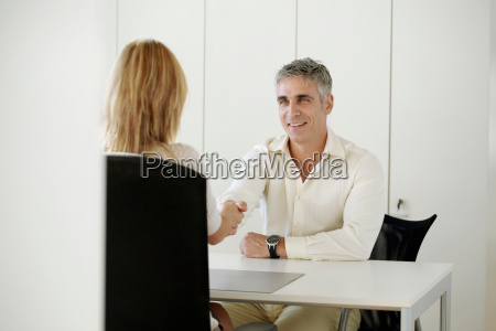 older man and woman shaking hands