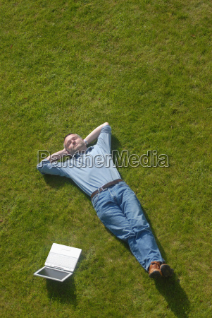 contented man relaxes on lawn with