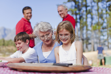 woman with grandchildren at picnic table