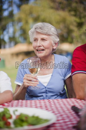 older woman drinking at picnic table