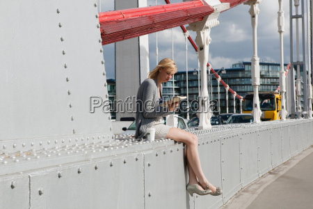 woman sitting on bridge looking at