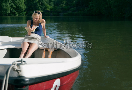 woman reading book on rowing boat