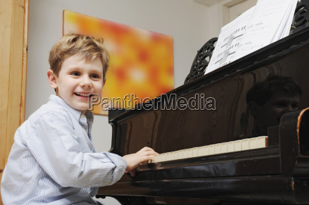boy playing the piano in living