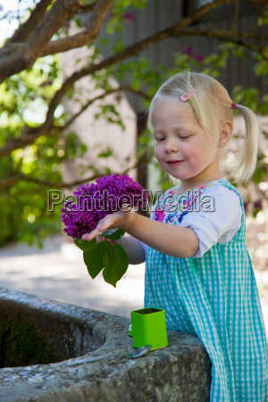 girl holding bunch of flowers outdoors