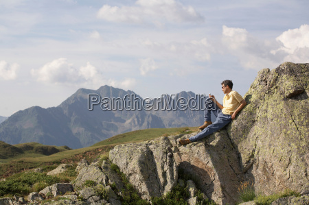 man on phone looking over mountains
