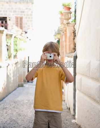 boy 8 10 taking photograph