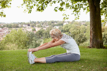 woman stretching hands to toes in