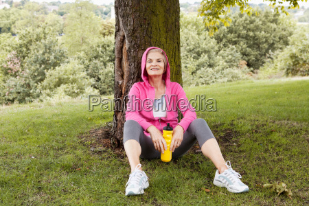 mature woman sitting against tree