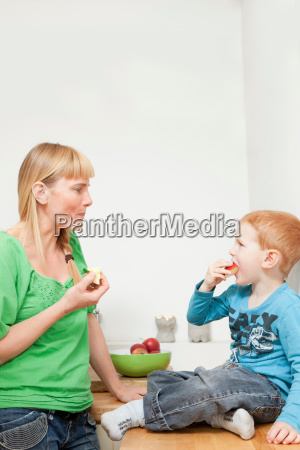 mother and son eating apples together
